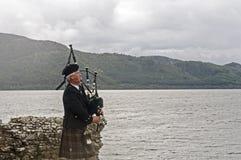 Scot que joga gaitas de fole na frente do lago Imagens de Stock
