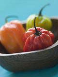 Scotch Bonnet Chilies In a Wooden Dish stock photo