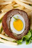 By scotch egg with french fries macro. Vertical Royalty Free Stock Image