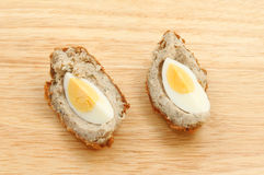 Scotch egg segments. On a wooden chopping board Royalty Free Stock Photography