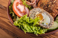 Scotch egg with vegetables. On a wooden background Stock Photo