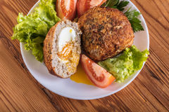Scotch egg with vegetables. On a wooden background Royalty Free Stock Images