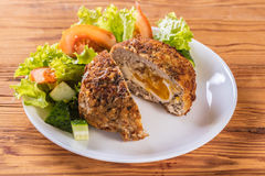 Scotch egg with vegetables. On a wooden background Royalty Free Stock Image