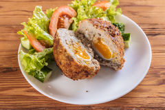 Scotch egg with vegetables. On a wooden background Stock Photography