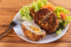 Scotch egg with vegetables. On a wooden background Stock Images