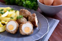 Scotch eggs with boiled potatoes. A plate of scotch eggs with boiled potatoes on a wooden background stock photos