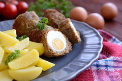 Scotch eggs with boiled potatoes. A plate of scotch eggs with boiled potatoes on a wooden background stock images