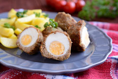 Scotch eggs with boiled potatoes. A plate of scotch eggs with boiled potatoes on a wooden background royalty free stock image