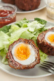 Scotch eggs cut in halves on a plate Stock Photos