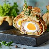 Scotch eggs in a pancake bag with greens on a gray-blue background. A classic dish in an unconventional serving. Delicious. And appetizing dish of British stock photography