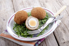 Scotch eggs on a plate with rocket salad Royalty Free Stock Photo