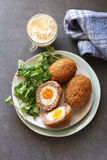 Scotch eggs on a plate with watercress salad Stock Photography