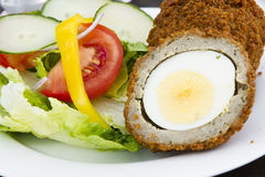 Scotch eggs. And salad on a plate Stock Images
