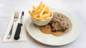 Scotch Fillet Steak. A scotch fillet steak with chips or french fries in mushroom sauce and pepper corns Stock Image