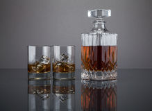 Scotch in a liquor decanter with tumblers. Two tumblers filled with liquor and ice, with a decanter full of liquid, isolated on a grey background Royalty Free Stock Photo