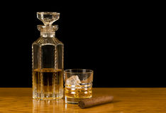 Scotch and scotch-rocks with cigar. 12 year scotch in crystal decanter, scotch rocks in glass, and cigar on oak bar top royalty free stock image