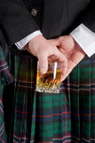 Scotch whiskey. Scotsman holding his glass of whisky behind is kilt Royalty Free Stock Images