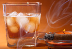 Scotch whiskey, a cigar and a candle. Scotch whiskey and a cigar burning in smoke Royalty Free Stock Photo