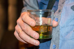 Scotch whiskey with ice. Man is holding a glass of scotch whiskey with ice Royalty Free Stock Photos