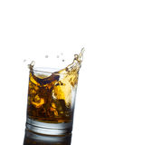 Scotch whiskey splashing out of glass. Isolated on Stock Image