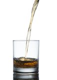 Scotch whiskey splashing out of glass. Isolated on Royalty Free Stock Photos