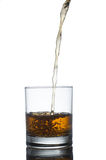 Scotch whiskey splashing out of glass. Isolated on Royalty Free Stock Photography