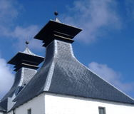 Scotch Whisky Distillery. The distinctive traditional chimneys of a whisky distillery in Scotland royalty free stock image