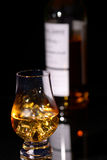 Scotch whisky. Glass of scotch with ice on a glass surface with bottle in background royalty free stock photos