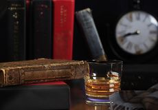 Scotch Whisky Neat with Books and Clock. A glass of whisky without ice or mixers, neat, with old leatherbound book and plaid scarf, blurred  books and clock  in stock photos