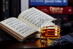 Scotch Whisky Neat with Books and Scarf. A glass of whisky without ice or mixers, neat, with plaid scarf in forground and books blurred in background, Open book royalty free stock photography