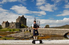 Piper at the Eilean Donan. Scotland, Dornie. Castle Eilean Donan and the young piper Royalty Free Stock Photography