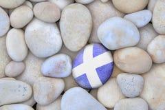 Scotland Flag Pebble. Scotland Pebble. Scottish flag pebble amongst white pebbles royalty free stock photography