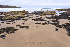 Scotland inscribed on wet yellow rocky beach sand Stock Image