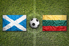 Scotland and Lithuania flags on soccer field Royalty Free Stock Photography