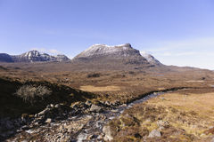 Scotland, Mountain, snow-capped in Spring. Stream and snowcapped mountain against blue Sky Royalty Free Stock Photo