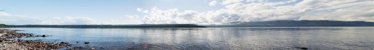 Scotland's Loch Ness. Panorama of Scotland's Loch Ness. Taken on the shoreline to capture the reflection during a sunny day Royalty Free Stock Photos