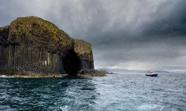 Rain showers and Staffa Island off the coast of Scotland. Scotland. Staffa island in the rain. Rain showers and boat are visible stock photography