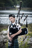 Scotland, UK - August, 2014 -Young man clad in a traditional scottish tartan playing the scottish bagpipe Stock Image