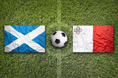 Scotland vs. Malta flags on soccer field. Scotland vs. Malta flags on a green soccer field Stock Photography