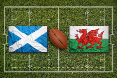 Scotland vs. Wales flags on rugby field Royalty Free Stock Image