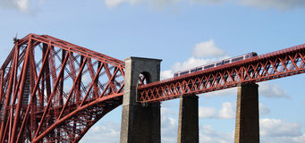 Scotrail train crossing Forth Bridge, Scotland. Scotrail liveried diesel multiple unit, crossing the iconic Forth Rail Bridge over the Firth of Forth, is seen on Royalty Free Stock Photos
