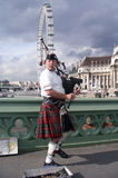 Scotsman with bagpipes. On the bridge on a background of London Eye and County Hall Stock Images