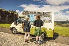 Scotsman, der einen Kilt und eine Frau vor dem Eiscremepackwagen trägt stockbild