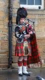 Scotsman en el vestido tradicional que toca las gaitas C Imagenes de archivo