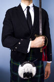 Scotsman holding sword. Young scotsman in kilt outfit posing with a sword Royalty Free Stock Photo