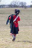 Scotsman piper marching to reenactment battle. In an English countryside field. Traditional reproduction Scots guard uniform Royalty Free Stock Photos