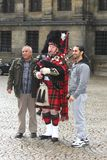 Scotsman is playing a bagpipe at Dam Square in the city centre of Amsterdam, Netherlands  Royalty Free Stock Photo