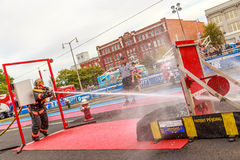 Firefighter World Combat Challenge XXIV. Picture of a female firefighter and competitor as she breaks through the swing door to water blast the target at the royalty free stock image