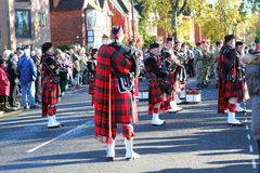 Scottish bagpipe band in kilts. A Scottish pipe band wearing traditional kilts. The band is standing in the street and preparing to play the bagpipes and drums stock image