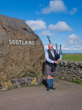 Scottish bagpiper at country border Royalty Free Stock Photography